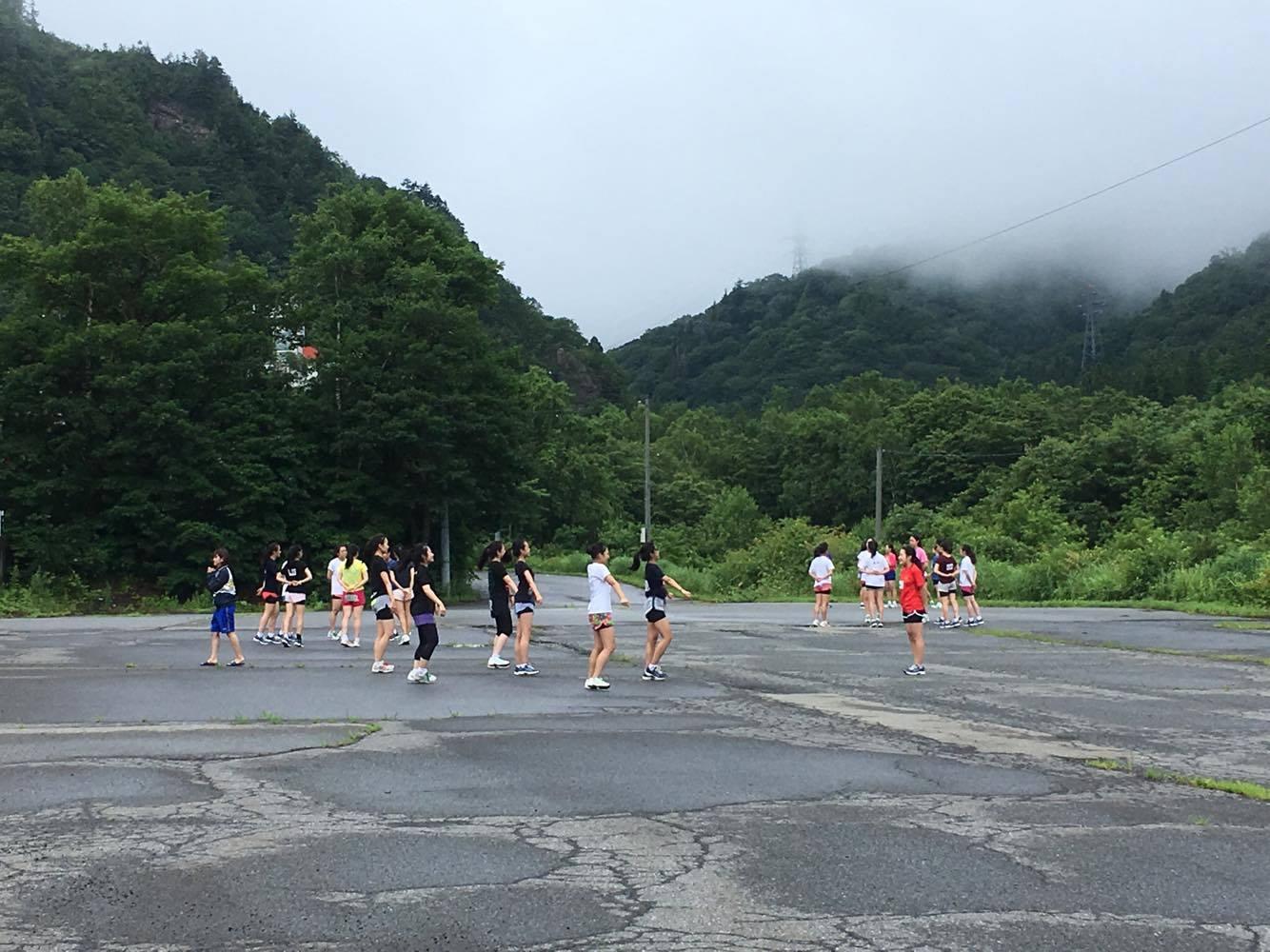 学生が場内駐車場で運動している風景