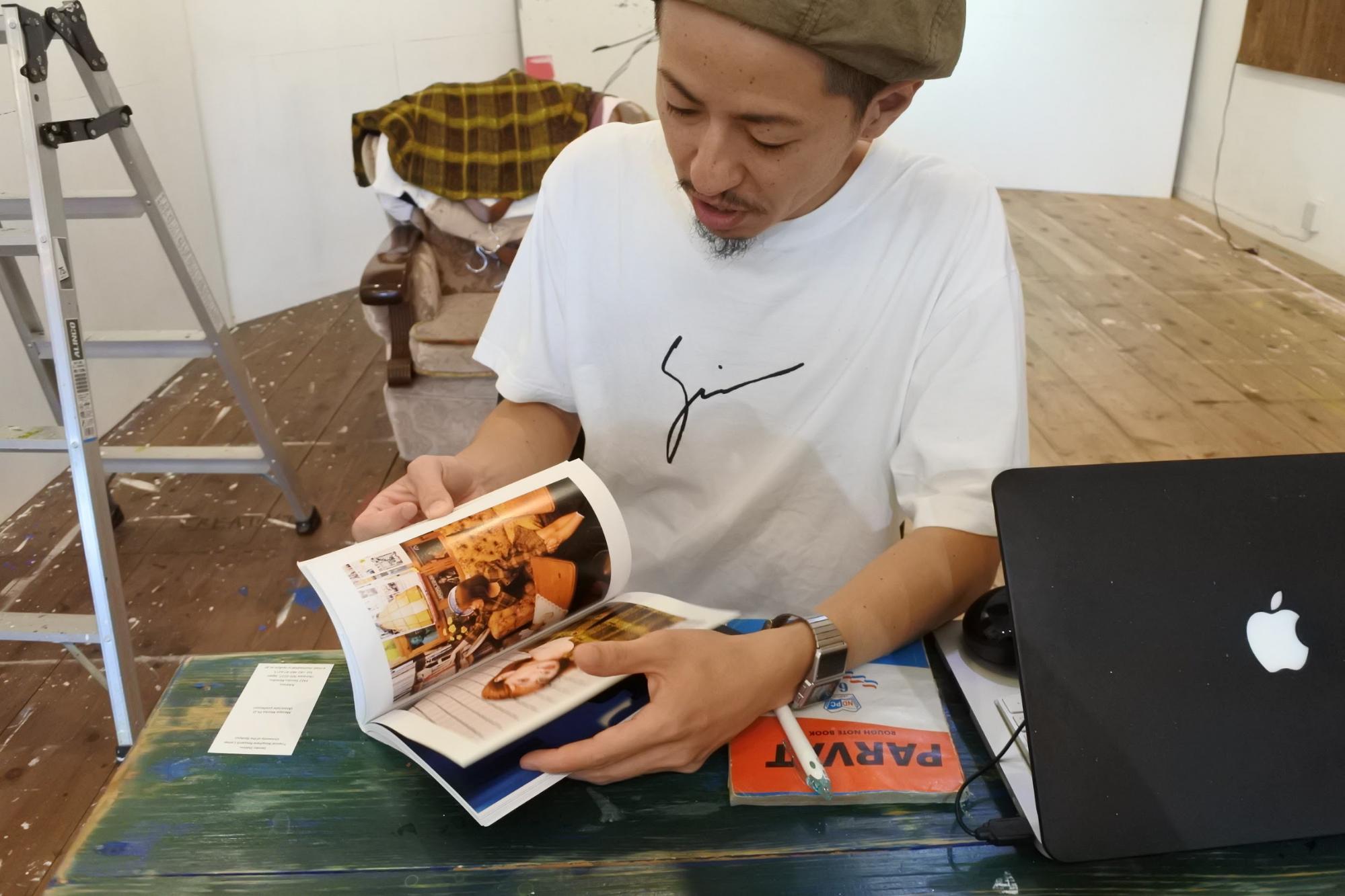 展覧会での写真集を手に | Photo by Masaya Morita